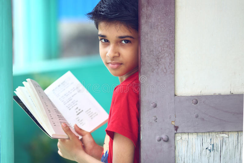 Индийский мальчик с учебником стоковое фото rf