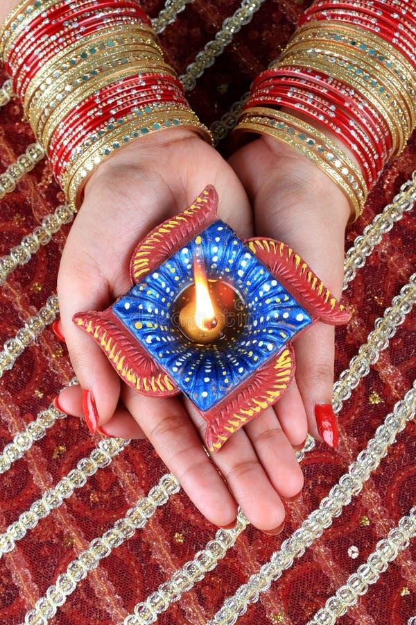Индийский свет лампы Diwali Diya фестиваля в женской руке стоковое изображение