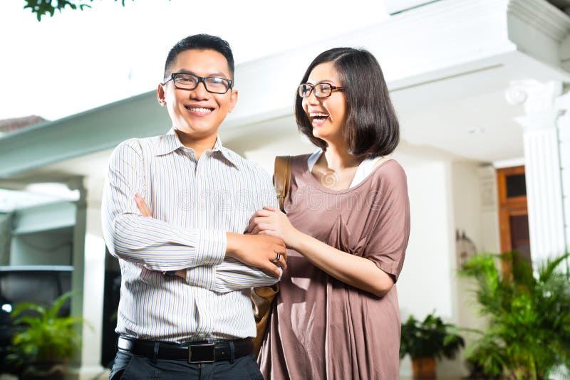 Азиатские пары владельца дома перед домом стоковое изображение rf