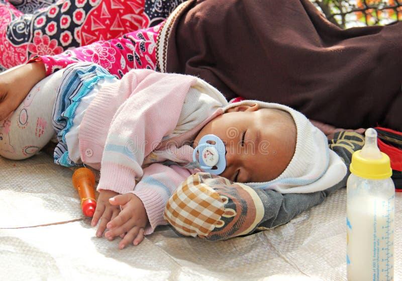 Индонезия, Джакарта 18-ое мая 2014 Женщина с умолять ребенка стоковое изображение rf