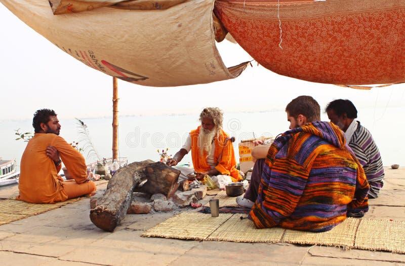 Индусские монах и следующие на речном береге, Варанаси стоковые фото