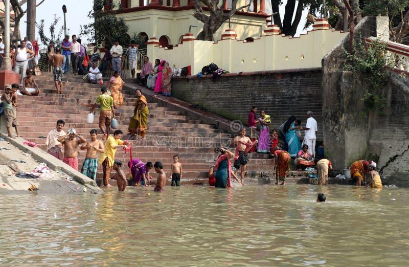 Индусские люди купая в ghat около виска Dakshineswar Kali в Kolkata стоковое фото rf