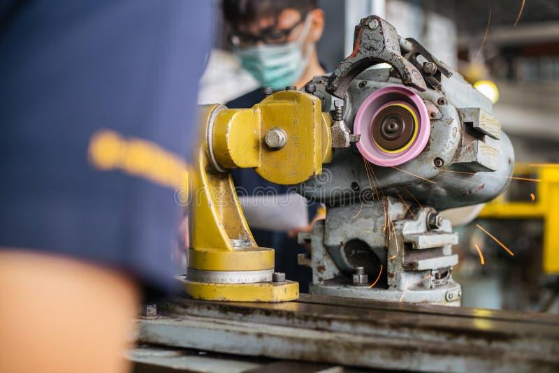 Индустрия механической обработки: металл отделкой работая на машине точильщика токарного станка стоковое изображение rf