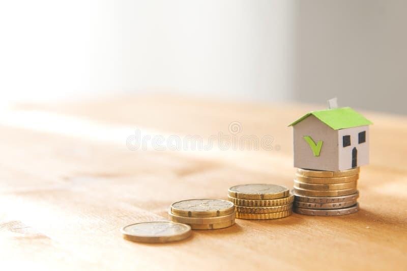 Ипотека и концепция займа: бумажный дом на куче монетки и s стоковые изображения