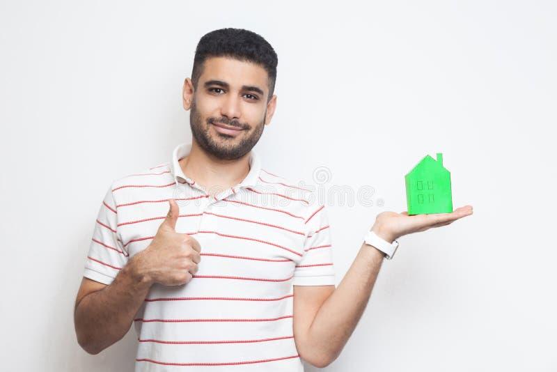 Ипотека - это хорошо Положительный привлекательный молодой человек в футболке, держащий зеленую бумагу в маленьком доме и предлаг стоковое изображение