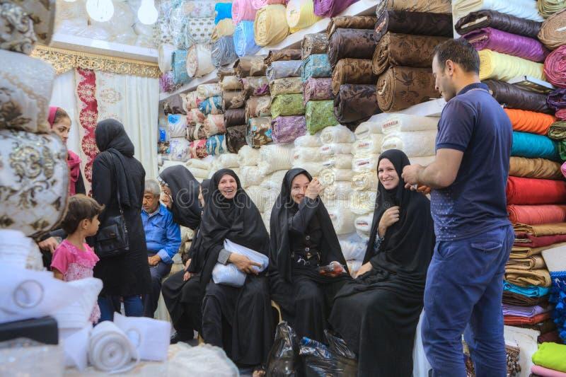 Иранские женщины в черном исламском платье ослабляют в магазине тканей стоковое изображение