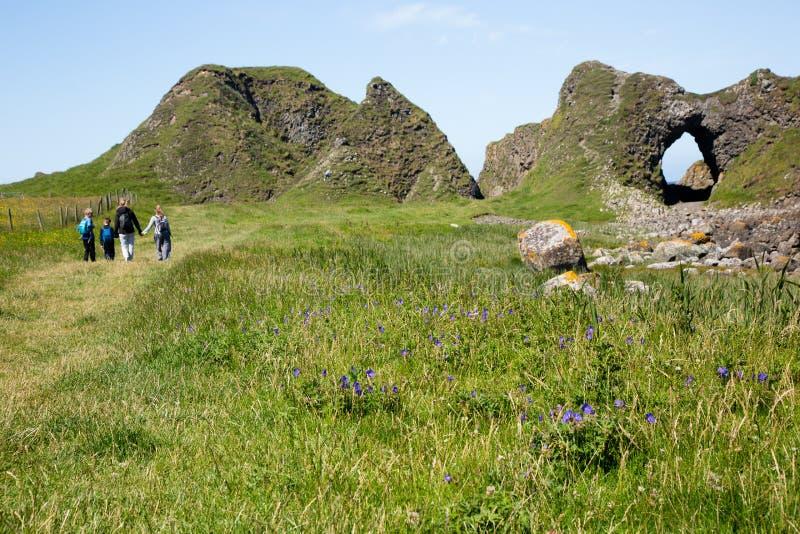 Ирландские благоустраивают, зеленая трава и похожие на пещера горные породы, пешая семья стоковое фото
