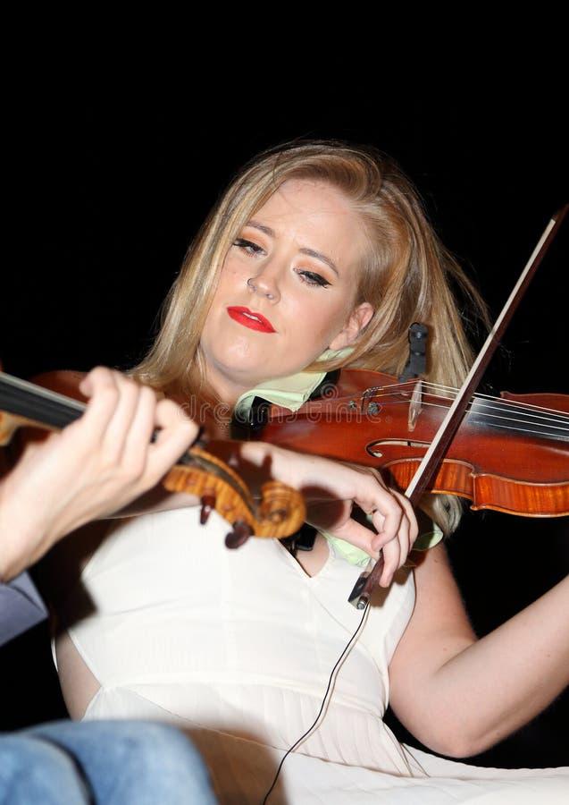 Ирландский Ni Bhriain Ciara скрипача выполняет вместе с группой дерева Birkin музыкальной стоковое изображение rf