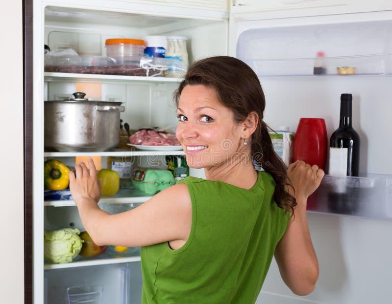 Искать женщины ест в холодильнике дома стоковые изображения rf