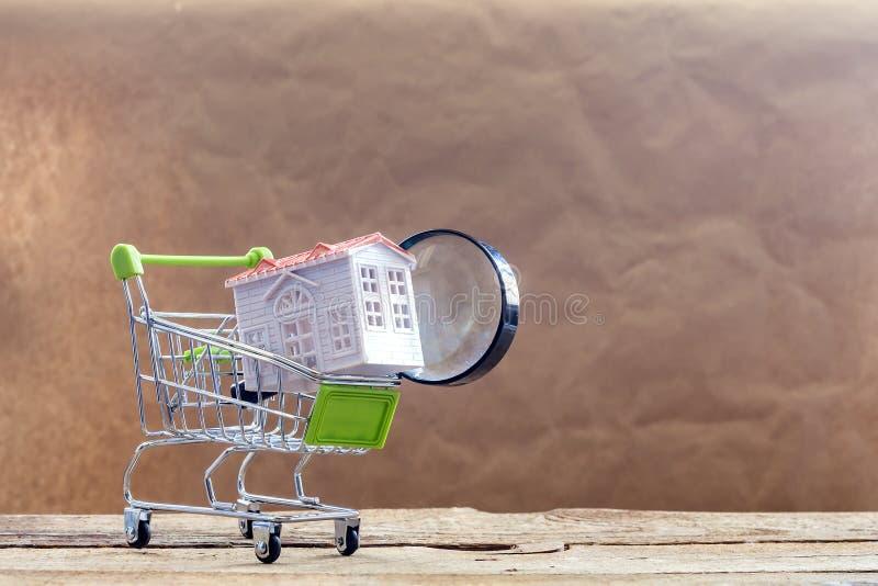 Искать новую домашнюю концепцию Миниатюрные модель и лупа дома в корзине Покупающ или продающ дом r стоковое фото
