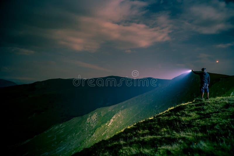 Искать с электрофонарем в горах стоковая фотография rf
