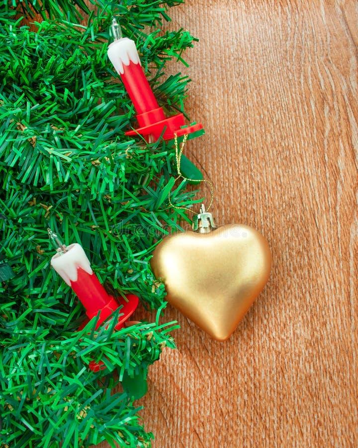 Искусственная рождественская елка, электрические свечи и золотое сердце стоковое фото rf