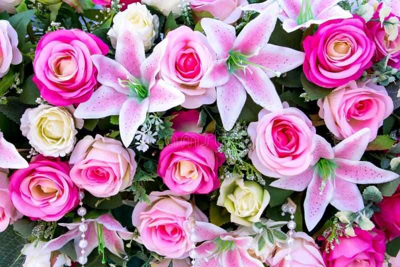 Искусственное розовое украшение букета цветков и лилий смешанное с предпосылкой шариков стоковая фотография rf