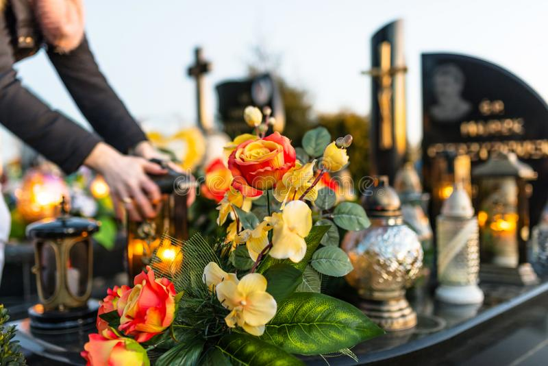 Искусственные и реальные цветки и освещенные свечи лежа на надгробной плите в кладбище стоковые фотографии rf