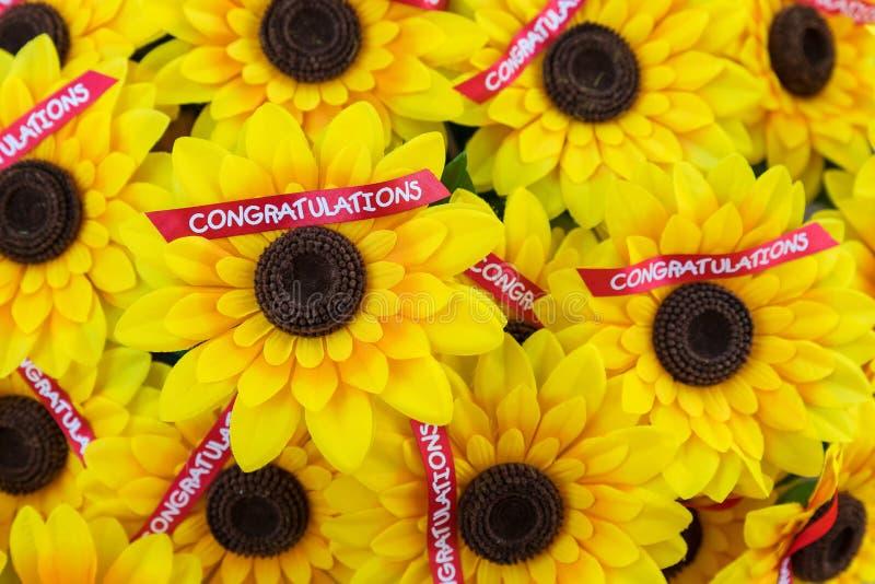 Искусственные солнцецветы с красной лентой поздравлениям на ей стоковая фотография rf