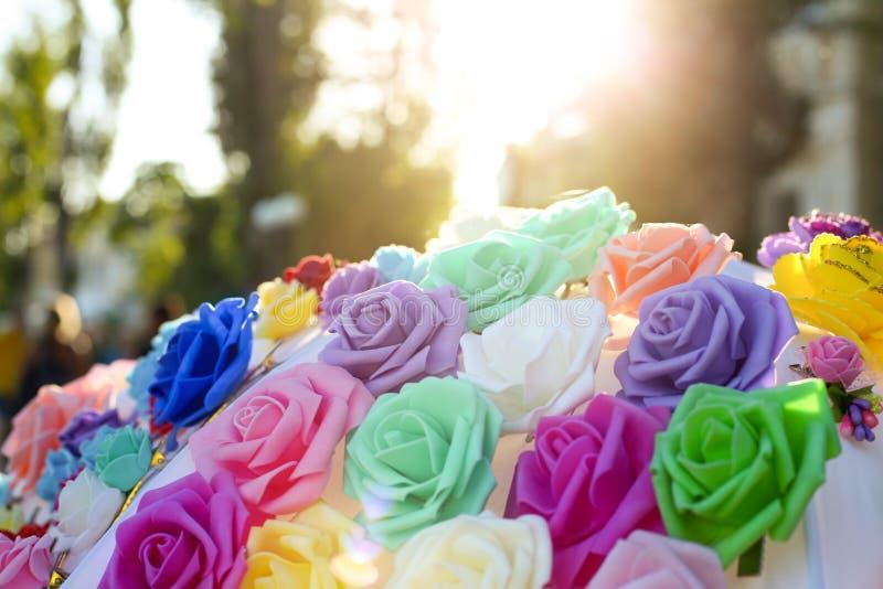 Искусственные цветки других цветов закрывают вверх на заходе солнца стоковые изображения rf