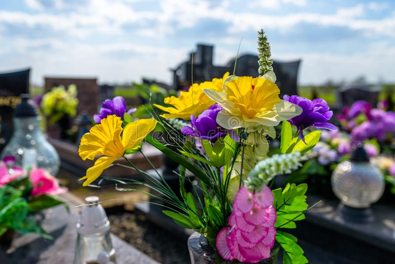 Искусственные цветки и подсвечники лежат на надгробной плите в кладбище стоковая фотография