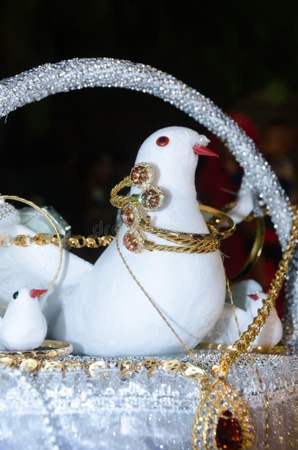 Искусственный белый голубь в корзине с браслетами и цепями золота с самоцветами стоковые фотографии rf