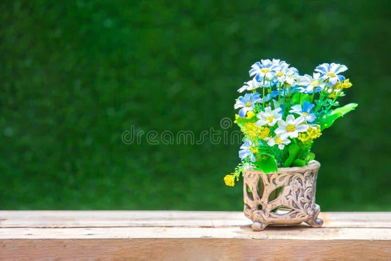 Искусственный красочного цветка в старой вазе на деревянном столе - S стоковое изображение