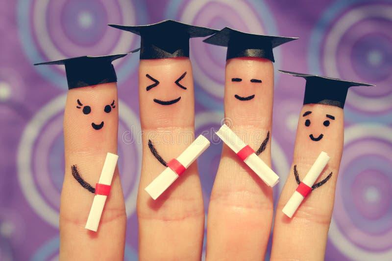 Искусство пальца студентов Студент-выпускники держа их диплом после градации стоковые изображения