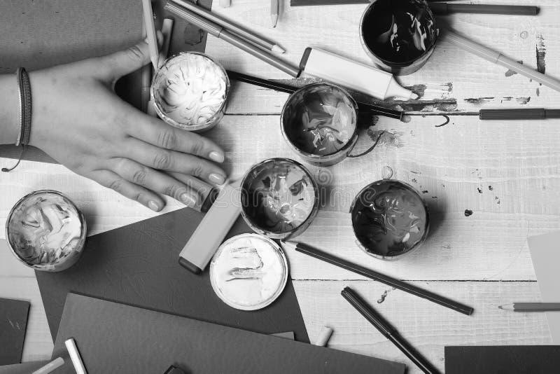 Искусство поставляет около женской руки на белой деревянной предпосылке стола, взгляд сверху Концепция искусства и идеи Рука держ стоковые изображения rf