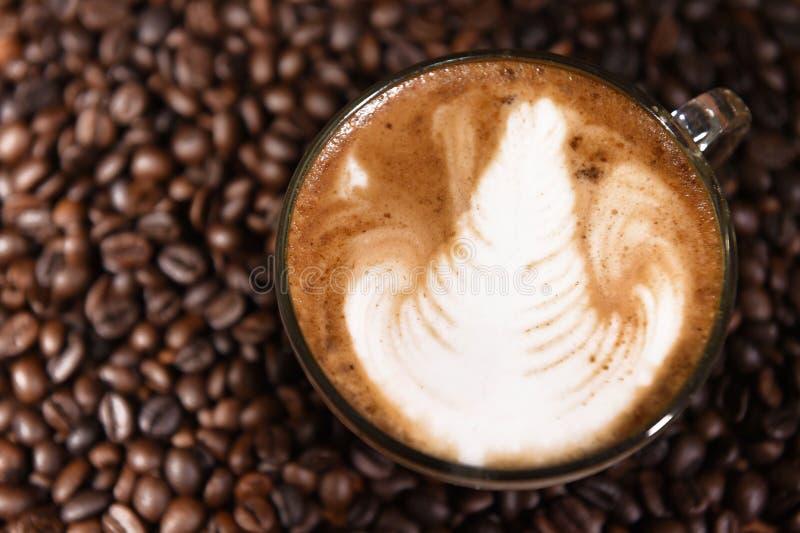 Искусство Latte, кофе в предпосылке кофейных зерен стоковые фото