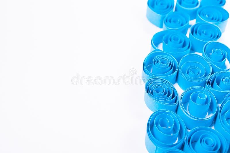Искусство Quilling Голубая бумага завивает на белой предпосылке стоковые изображения rf