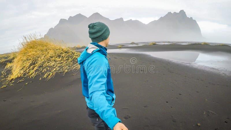 Исландия - молодой человек принимая selfie с горами на пляже отработанной формовочной смеси стоковое изображение rf