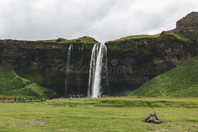 ИСЛАНДИЯ - 20-ОЕ ИЮНЯ 2018: красивый водопад Seljalandsfoss и туристы под пасмурным стоковое фото rf
