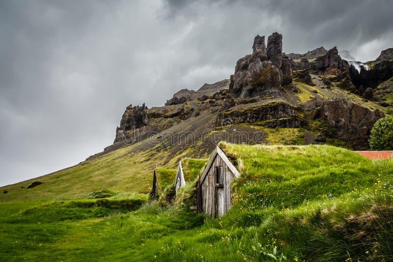 Исландские дома дерновины покрытые с травой и скалами в backg стоковое фото rf