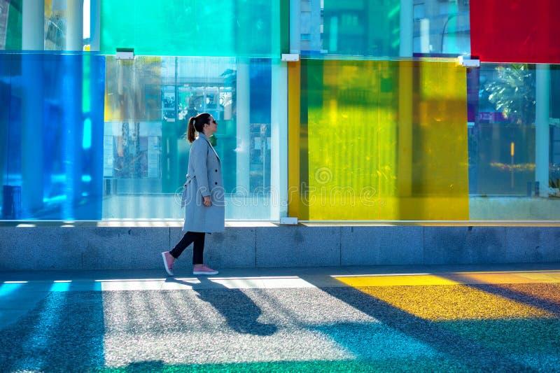 Испания, Малага - 04 04 2019: Женщина идя рядом с красочным центром Pompidou куба в Малага, Испании в солнечности стоковая фотография rf