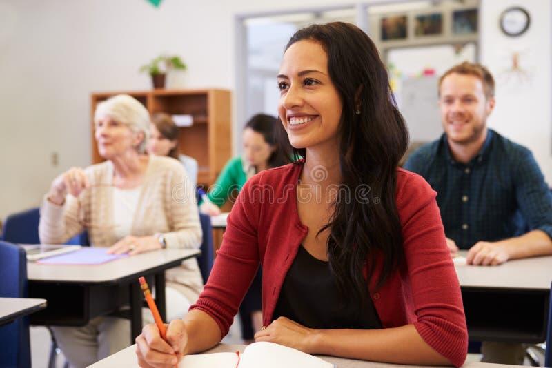 Испанская женщина изучая на классе обучения взрослых смотря вверх
