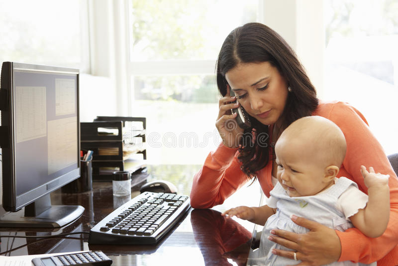 Испанская мать при младенец работая в домашнем офисе