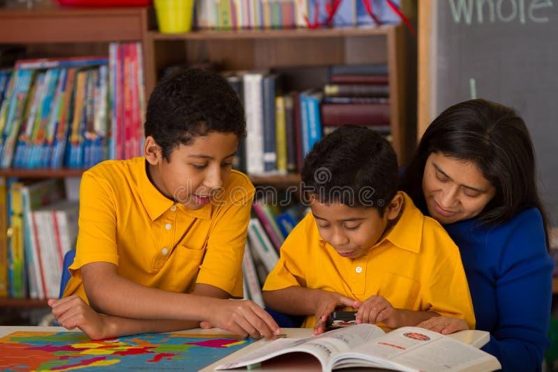 Испанские мальчики с мамой в окружающей среде Дом-школы стоковые фотографии rf