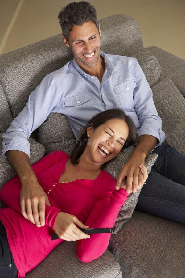 Испанские пары на софе смотря ТВ стоковые фотографии rf