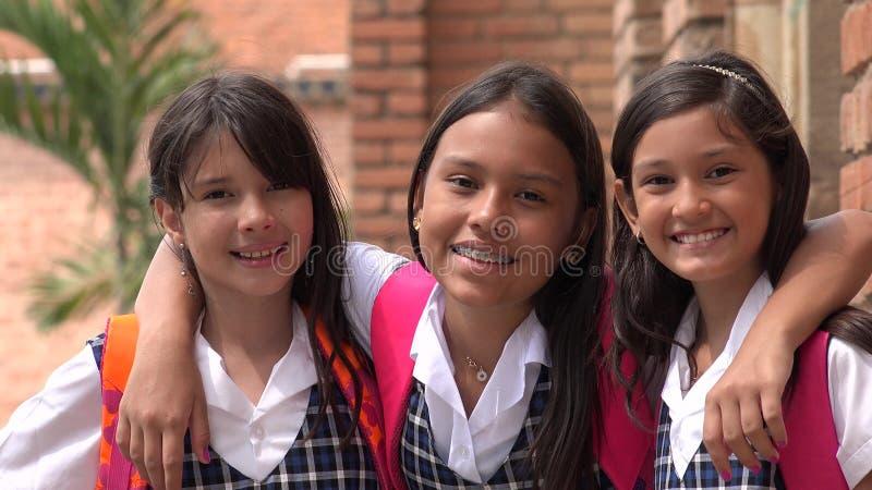 Испанские студенты девушки и школьные формы приятельства нося стоковая фотография