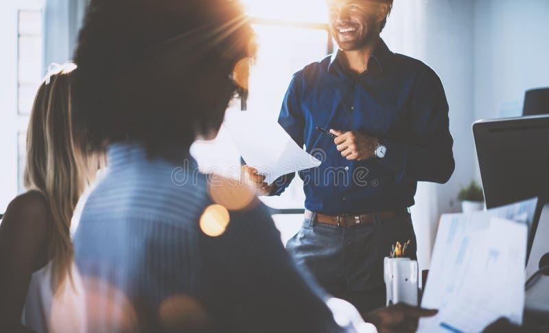 Испанский бизнесмен держа руки и усмехаться бумаг Молодая команда сотрудников делая большое обсуждение дела в современном стоковое фото rf