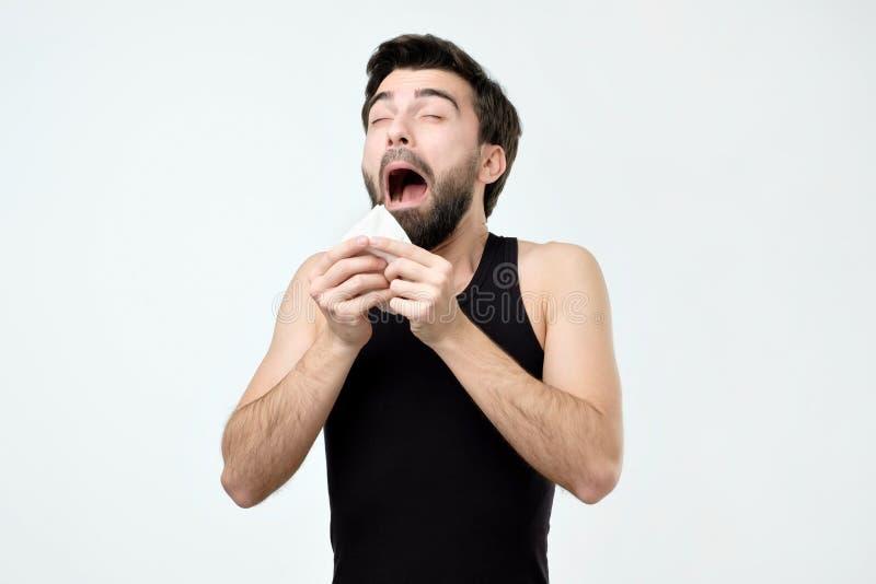 Испанский молодой человек с черной бородой быть больной чихать стоковая фотография rf