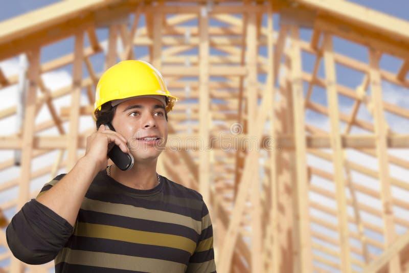 Испанский мужской подрядчик на телефоне перед обрамлять дома стоковое изображение