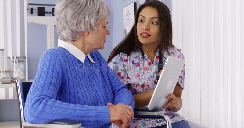 Испанский попечитель разговаривая с таблеткой с пожилым пациентом стоковые фото