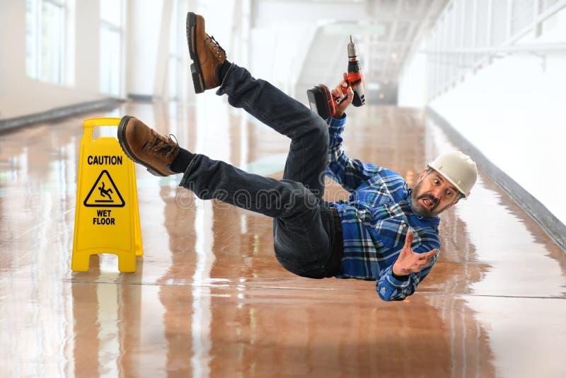 Испанский работник падая на влажный пол стоковые фото