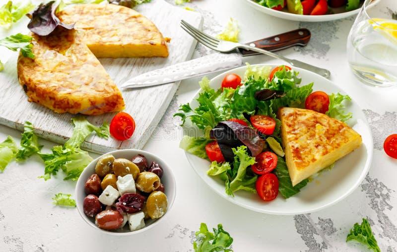 Испанский tortilla, омлет с картошкой, лук, овощи, томаты, оливки и травы в белой плите Завтрак стоковые фотографии rf