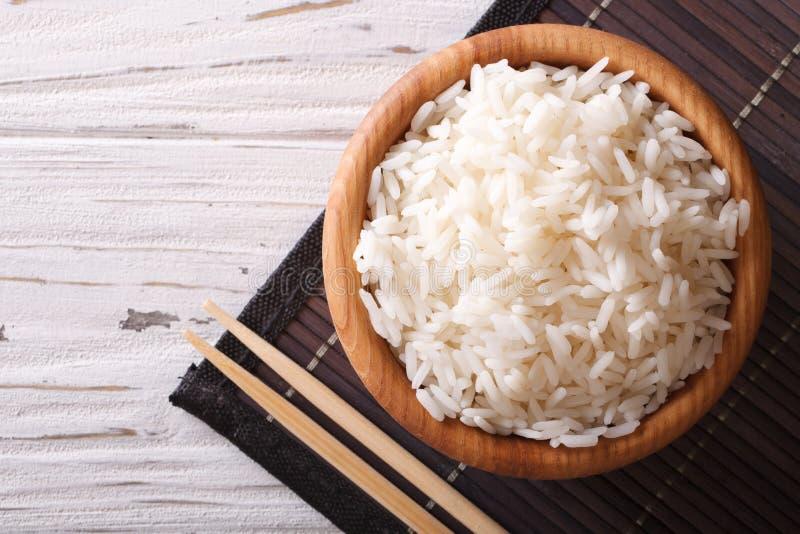 Испаренный рис в деревянном шаре и палочках Горизонтальная верхняя часть соперничает стоковая фотография rf