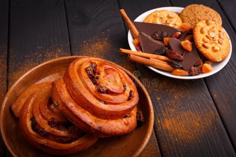 2 испекли плюшки с вишнями и печеньями на плитах на таблице внутрь стоковые изображения rf