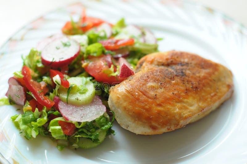 Испеченная куриная грудка с vegetable салатом на белой плите стоковые фотографии rf