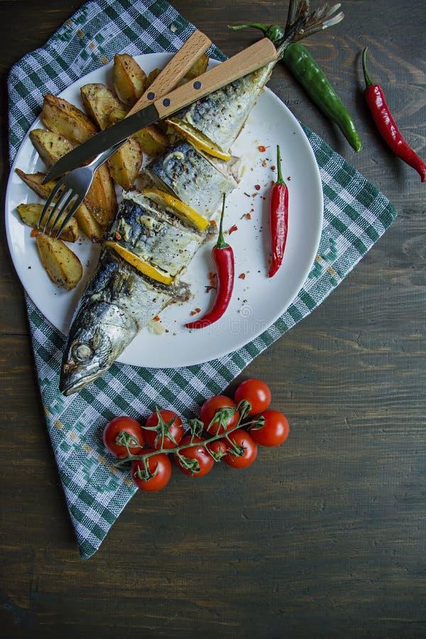 Испеченная скумбрия с лимоном и печеными картофелями на белой плите t Вишня, перец chili cutlery r стоковые фото