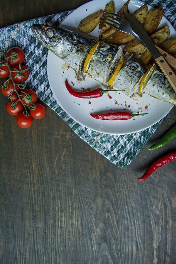 Испеченная скумбрия с лимоном и печеными картофелями на белой плите t Вишня, перец chili cutlery r стоковые изображения rf