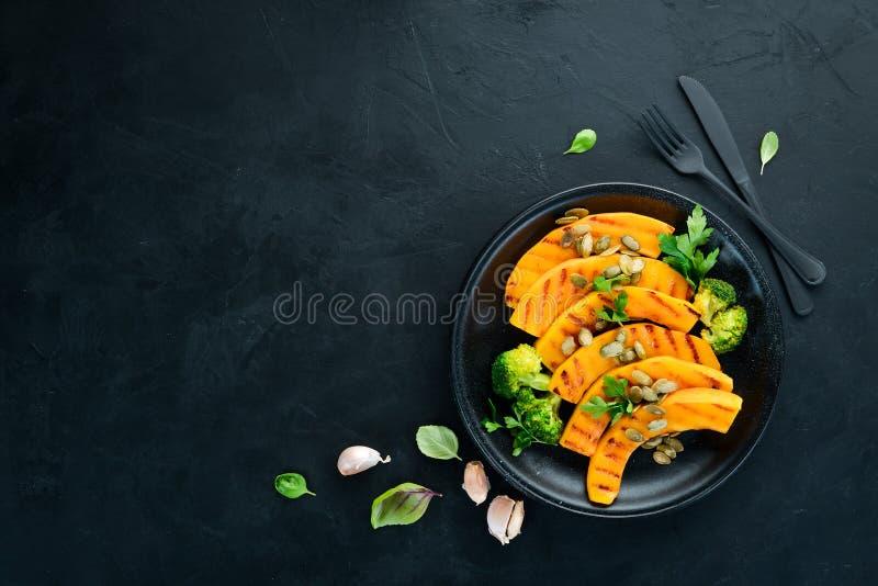 Испеченная тыква с семенами и брокколи тыквы На черной предпосылке стоковая фотография rf