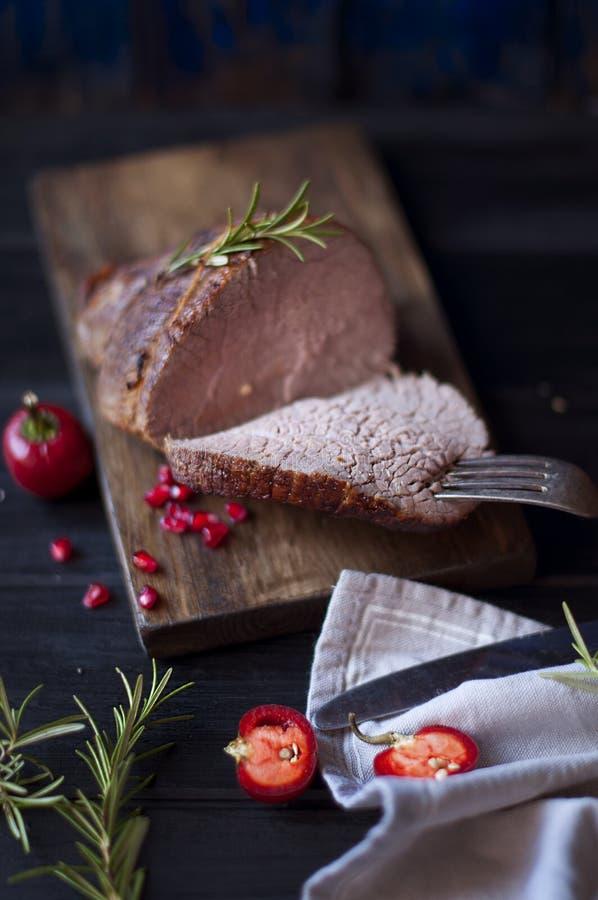 Испеченное мясо с розмариновым маслом и красным перцем Стейк bedroll обедающий для людей Темное фото Черная предпосылка Деревянна стоковые фото