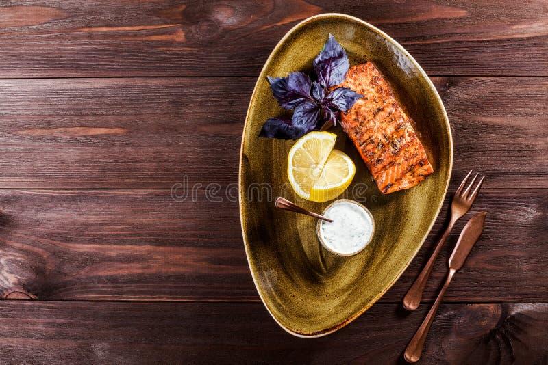 Испеченное филе семг с соусом, базиликом и лимоном сыра на плите на деревянной предпосылке рыбы тарелки горячие стоковая фотография